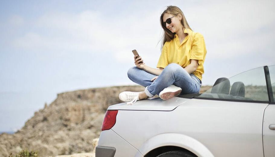 young lady sitting at the back of her car holding her mobile phone